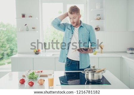 Doubt questions man in denim jeans shirt wear make brunch with vegetables vitamins vermicelli hold cookbook in hand scratching head stand inside bright flat