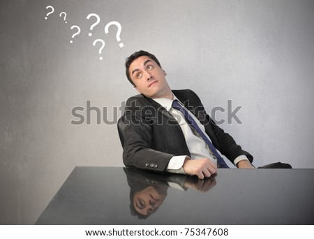 Doubtful businessman with question marks over his head