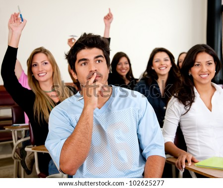 Doubtful man amongst a group of university students in a classroom rising their hands