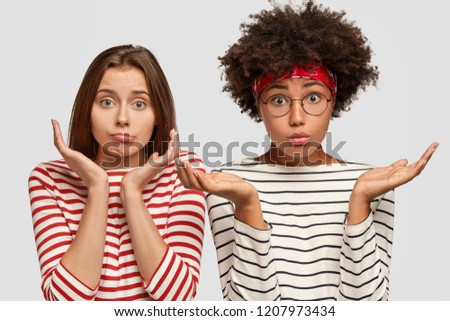 Doubtful two young clueless girls spread palms, have uncertain facial expressions, cant make desicion what topic for project work to choose, wear striped clothes, isolated over white background
