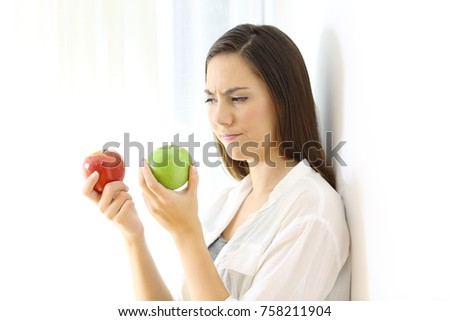 Doubtful woman deciding between red and green apples isolated on white at side Stock foto ©