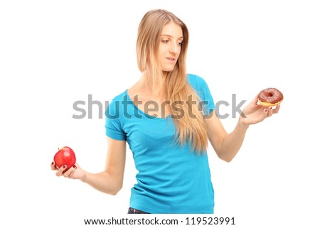 Doubtful woman holding an apple and donut trying to decide which one to eat