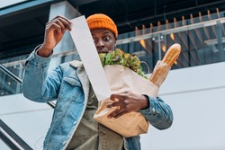 Doubting African-American person in denim jacket looks at sales paper receipt total holding pack with food products on escalator