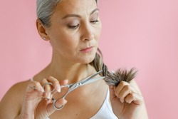 Doubting middle aged Asian woman cuts frayed ends of long grey hair with scissors on pink background in studio. Mature beauty lifestyle