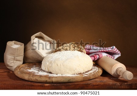 Dough and bags with flour on wooden table on brown background