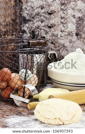Dough and fresh butter, eggs and flour for making biscuits or bread. Shallow depth of field.