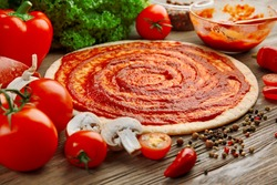 Dough basis with ketchup and ingredients for pizza, on the table