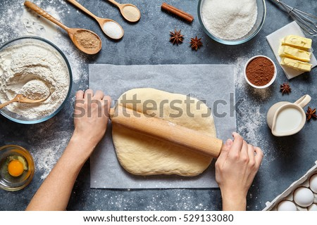 Dough bread, pizza or pie recipe homemade preparation. Female baker hands rolling dough with pin. Food ingridients flat lay on kitchen table. Working with pastry or bakery cooking. Top view