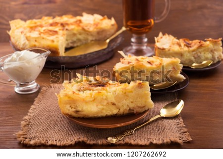 Dough cake with curd layer, cut into portions, wooden background.