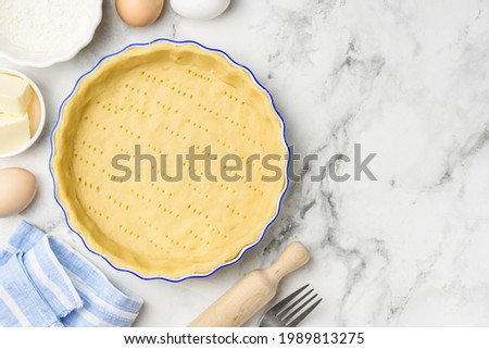 Dough for baking quiche tart pie in ceramic form. Culinary concept. Flat lay. Сopy space