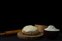 Dough on a dark background. A piece of homemade dough on a wooden board on a black background. The tools for working with the baking dough lie around the dough.