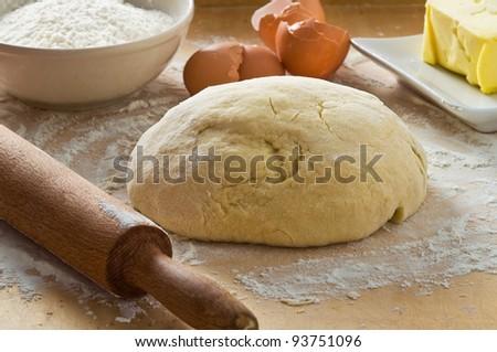 Dough on wooden board.