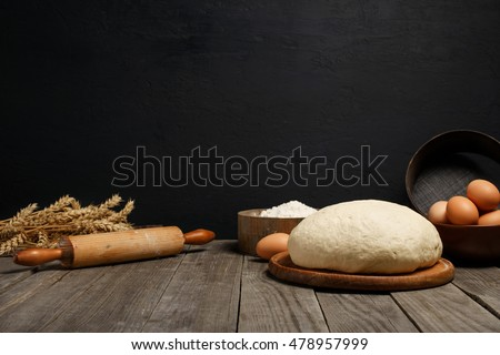 Dough on wooden table on dark background with space for an object in a bakery