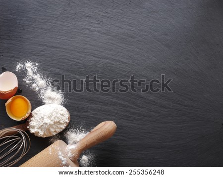 Dough preparation. Baking ingredients: egg and flour on black board.
