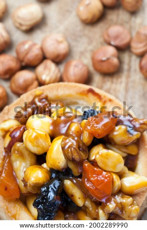 dough tartlet nuts and dried fruits covered with caramel, small round tartlet with a variety of fillings, crispy tartlet with hazelnuts, peanuts and other ingredients