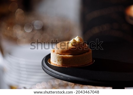 dough tartlet nuts with caramel on black tray, small round tartlet with a variety of fillings, crispy tartlet with hazelnuts, peanuts and other ingredients. selective focus