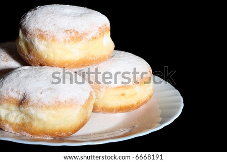 Doughnuts on white glass plate, isolated on black background