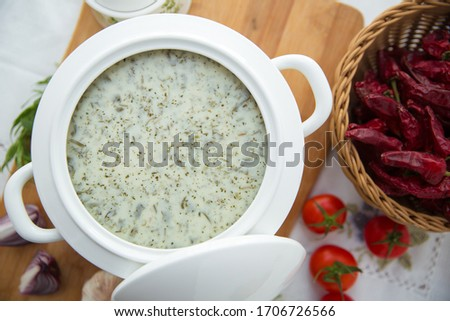 Dovga in the on wooden board . National food of azerbaijan . Creamy soup dovga . Azerbaijani Dovga soup with greens on a white bowl . Red tomato . Red Dry Pepper in Traditional Basket .