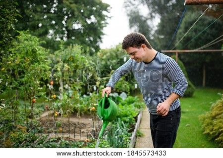 Down syndrome adult man watering plants outdoors in vegetable garden, gardening concept. Сток-фото ©