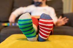 Down syndrome awareness concept. Boy wearing different socks while sitting on sofa at home. Different socks as symbol of down syndrome. Selective focus.