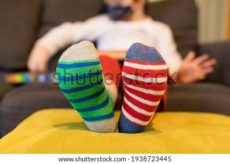 Down syndrome awareness concept. Boy wearing different socks while sitting on sofa at home. Different socks as symbol of down syndrome. Selective focus. Foto stock ©