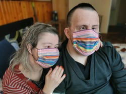 Down syndrome couple with respirator mask. Danger covid19 coronavirus.
