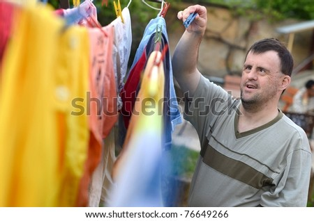 down syndrome man hanging clothes