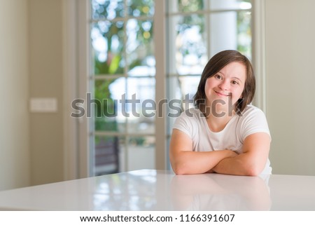 Down syndrome woman at home happy face smiling with crossed arms looking at the camera. Positive person.