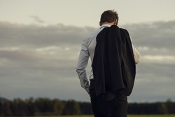 Downhearted businessman standing outdoors in evening light with his jacket slung over his shoulder staring down at the ground viewed from behind.