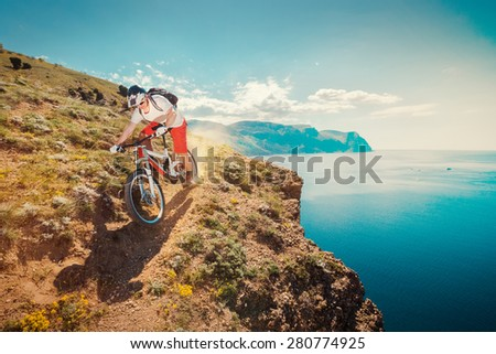 Downhill bike. Down from the mountain on a mountain bicycle. Extreme sport. Man riding outdoors lifestyle trail.