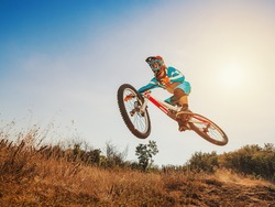 Downhill cycling. Man high jump on a mountain bike. Extreme sport.