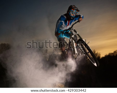Downhill cycling. Man jump on a mountain bike with dust. Extreme sport.