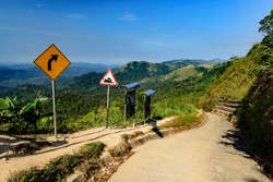 Downhill road through mountainside landscape with turn right and downhill sign on sunny day; Thailand-Myanmar Boarder-
