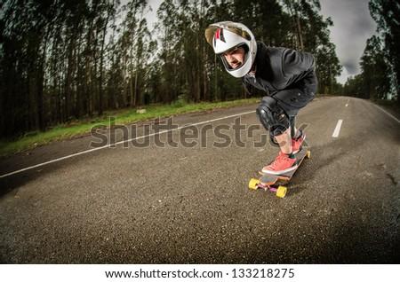 Downhill skateboarder in action on a asphalt road.
