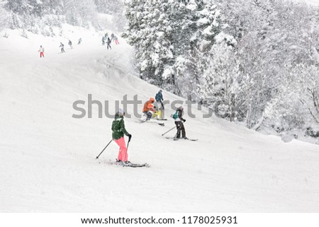 Downhill skiing during a heavy snowfall. Group of tourists, adults and children, on a resort slope in Andorra.