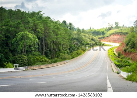 Downhill way, street or route which is surrounded by naturall hill side in the day time. Beautiful perspective line and curve. Land transportation photo concept. #1426568102