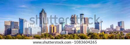 Downtown Atlanta Skyline showing several prominent buildings and hotels under a blue sky.