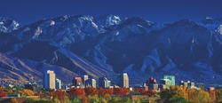 Downtown city skyline of Salt Lake City, Utah, with the Wasatch mountains in the background in afternoon sunshine.