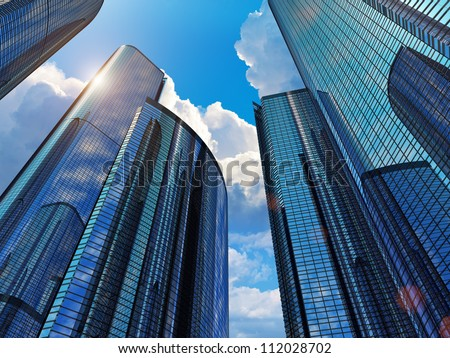 Downtown corporate business district architecture: glass reflective office buildings against blue sky with clouds and sun light