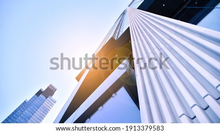 Downtown corporate business district architecture. Glass reflective office buildings against blue sky and sun light. Economy, finances, business activity concept.