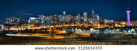 Downtown Denver, Colorado night city skyline on West side with streetlights and buildings for urban landscape.