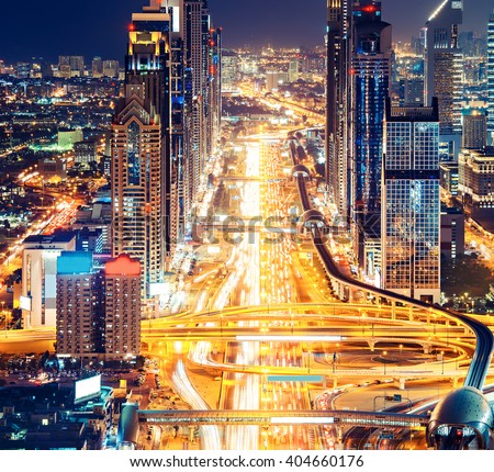 Downtown Dubai architecture by night. Aerial view of illuminated skyscrapers and highway. Famous travel destination.