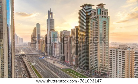 Downtown Dubai towers in the evening timelapse. Aerial view of Sheikh Zayed road with skyscrapers at sunset. Traffic on the road and metro line. Beautiful orange sky