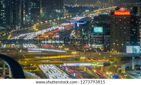 Downtown Dubai towers night . Aerial view of Sheikh Zayed road with skyscrapers. Traffic on the road and metro line. Blinking lights and trails