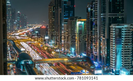 Downtown Dubai towers night timelapse. Aerial view of Sheikh Zayed road with skyscrapers. Traffic on the road and metro line. Blinking lights and trails