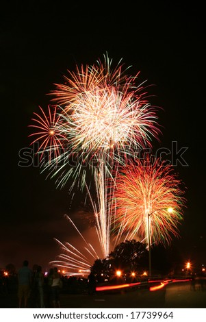Downtown fireworks display. Time elapse image capturing multiple bursts. Silhouette crowd in the foreground with streetlights. - stock photo