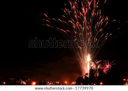 Downtown fireworks display. Time elapse image capturing multiple bursts. Silhouette crowd in the foreground with streetlights.
