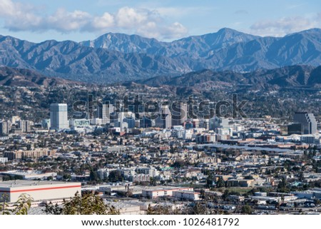 Downtown Glendale with the San Gabriel Mountains in background.  View from hilltop at Griffith Park in Los Angeles California.