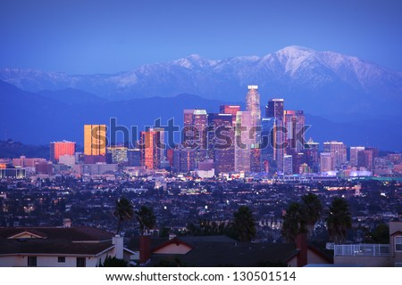 Downtown Los Angeles skyline over snowy mountains at twilight. - stock photo