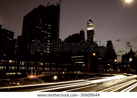 Downtown Manhattan with car light trails and a police car